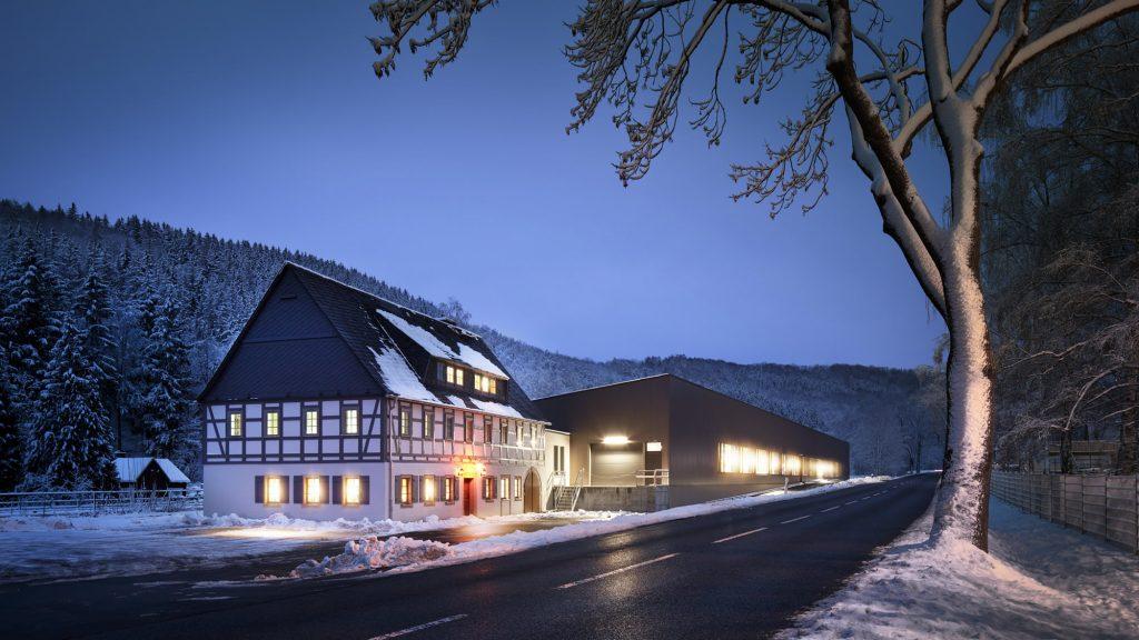 Die große Hydromatenhalle angrenzend an ein Fachwerkhaus bei Dunkelheit in Altenberg. Drinnen brennt Licht.