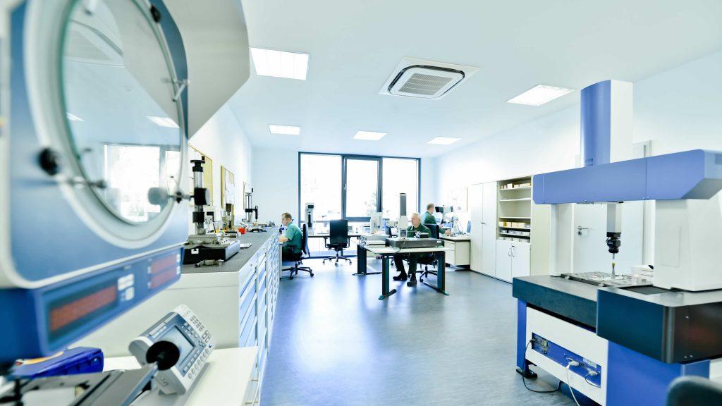 QS-Labor mit drei Mitarbeitern, die Maschinen bedienen.